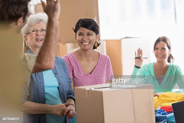 Cheerful female small business owners greet delivery person