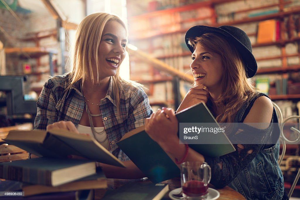 Cheerful female students talking to each other in a library. : Stock Photo
