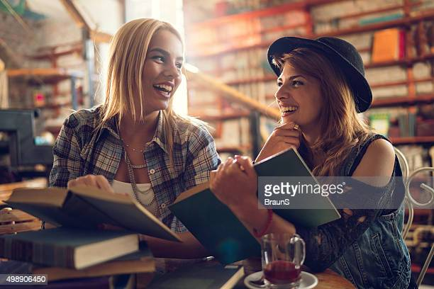 Cheerful female students talking to each other in a library.