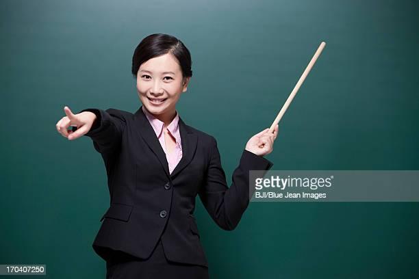 Cheerful female teacher pointing forward in classroom