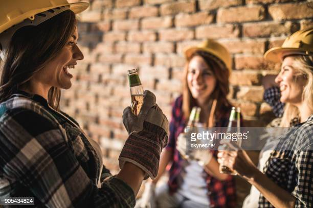 Cheerful female workers drinking beer on a break at construction site.