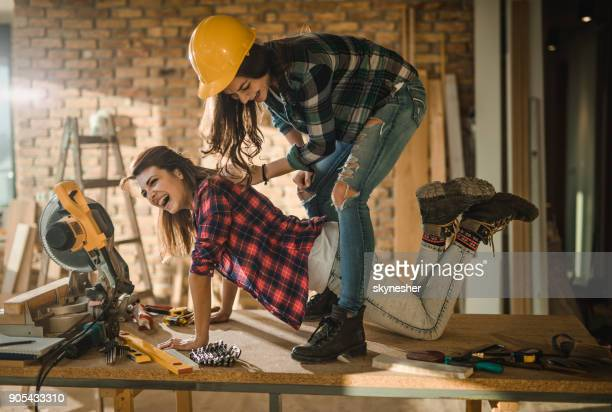 cheerful female workers having fun on the table at construction site. - building maintenance stock photos and pictures