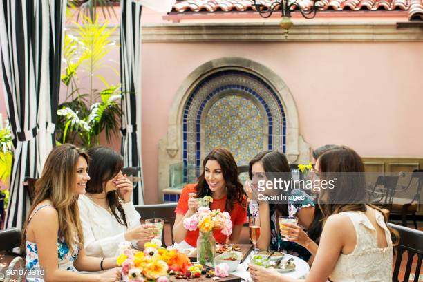 cheerful females talking at outdoor restaurant - gossip stock pictures, royalty-free photos & images