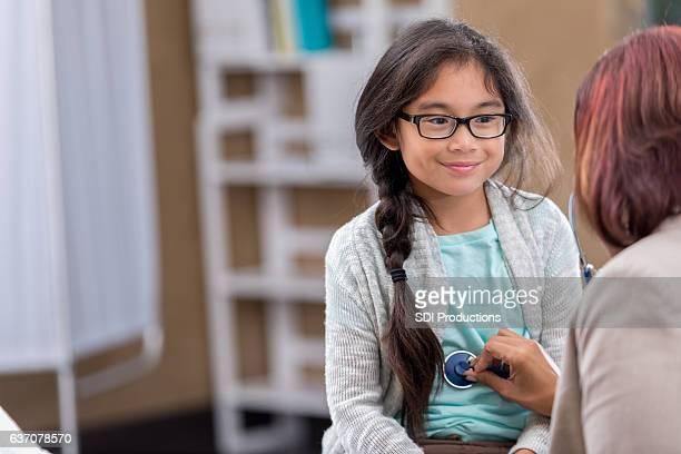 Cheerful Filipino girl smiles during well check exam