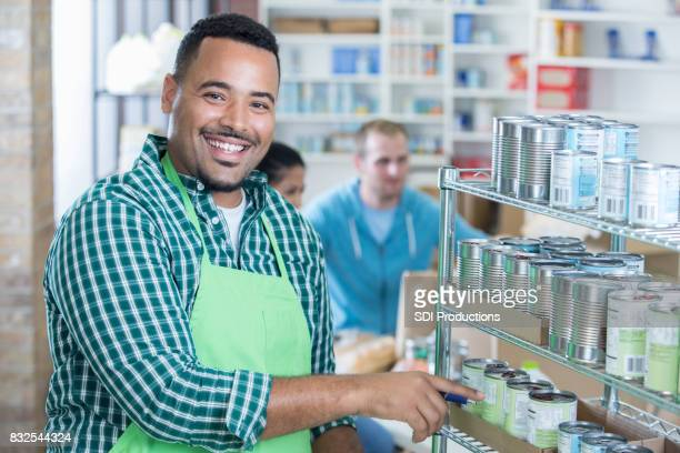 Cheerful food bank director works on inventory in storeroom