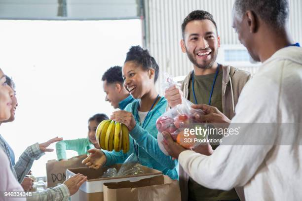 cheerful food bank volunteers receiving donations - food pantry stock pictures, royalty-free photos & images