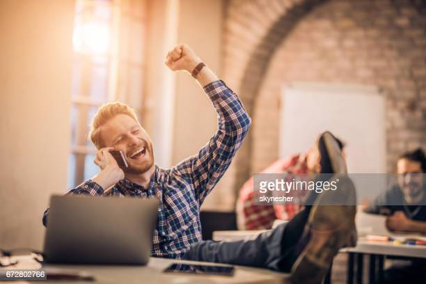 Cheerful freelance worker celebrating good news he hears over cell phone in the office.