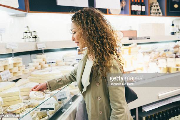 Cheerful french woman shopping cheese in a supermarket
