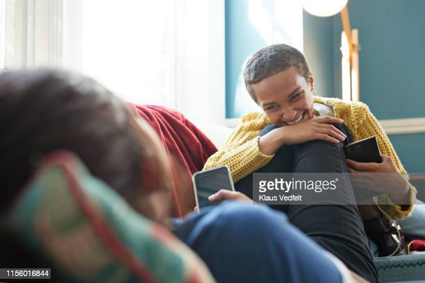 cheerful friend listening to woman at home - comfortable stock pictures, royalty-free photos & images