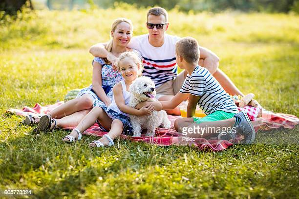 Cheerful friendly family is resting in park