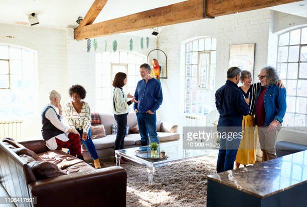cheerful friends chatting at party in open plan apartment - 50 54 years stock pictures, royalty-free photos & images