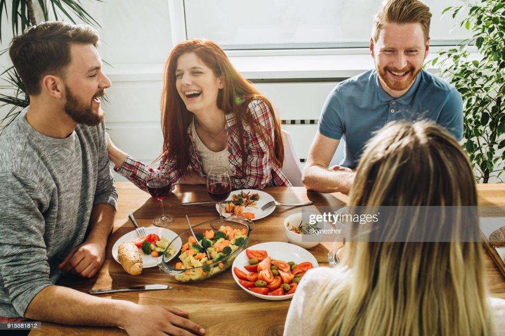 Fröhlichen Freunden kommunizieren und genießen Sie eine Mahlzeit am Esstisch. : Stock-Foto