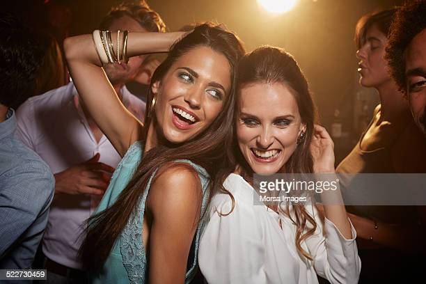 Cheerful friends dancing at nightclub