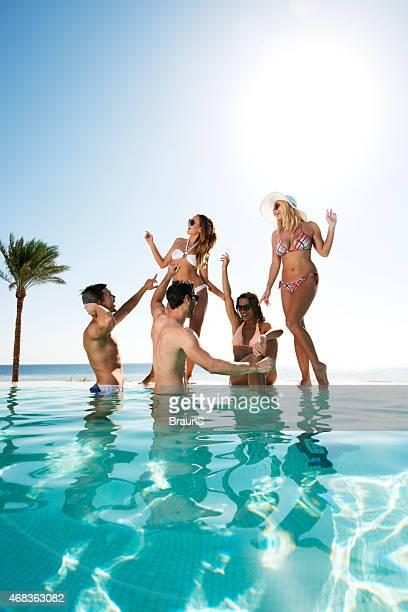 Cheerful friends dancing at swimming pool and having fun,