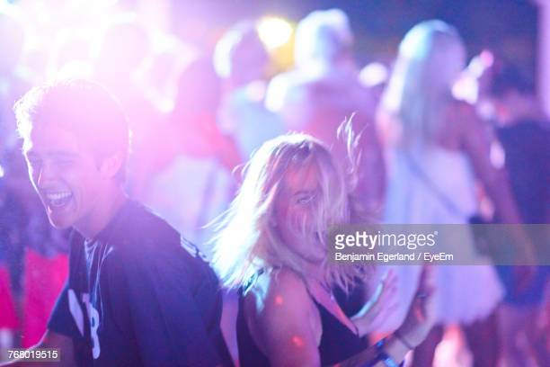 Cheerful Friends Dancing During Music Festival At Night