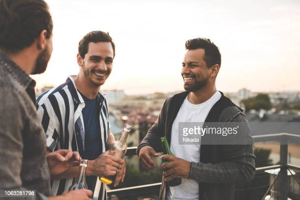 cheerful friends enjoying at rooftop party - only men stock pictures, royalty-free photos & images