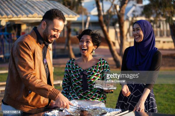 cheerful friends enjoying barbecue at beach - community stock pictures, royalty-free photos & images