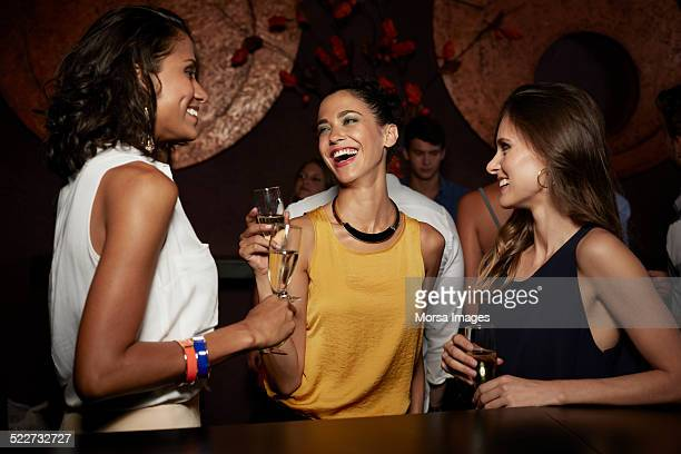 Cheerful friends enjoying champagne in nightclub