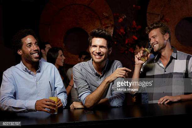 cheerful friends enjoying drinks in nightclub - comptoir de bar photos et images de collection