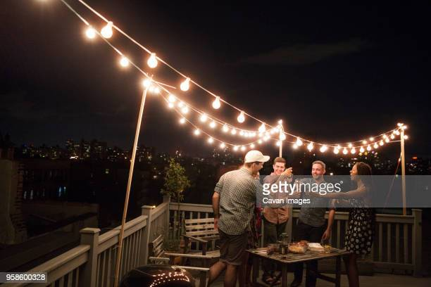 cheerful friends enjoying drinks on building terrace at party - building terrace stock pictures, royalty-free photos & images