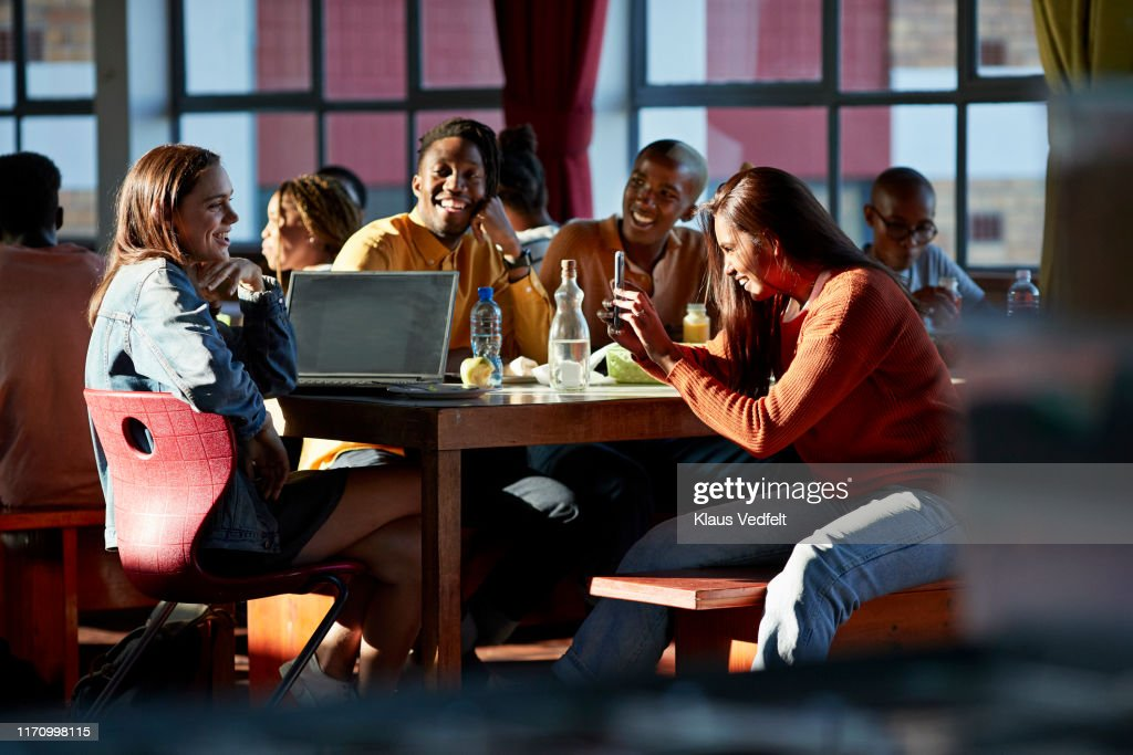 Cheerful friends enjoying during lunch break : Stock Photo