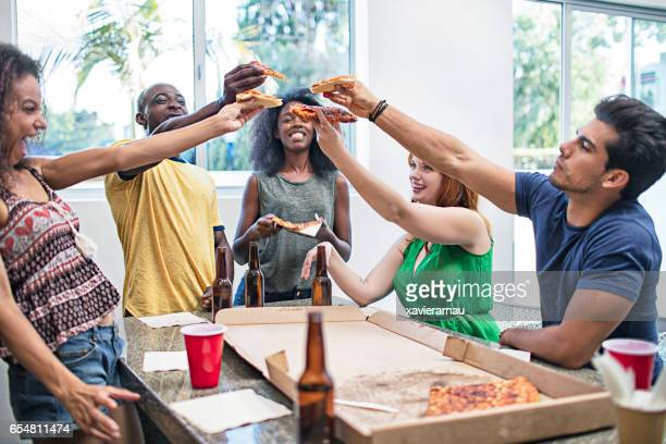 Cheerful friends enjoying pizza and beer at home