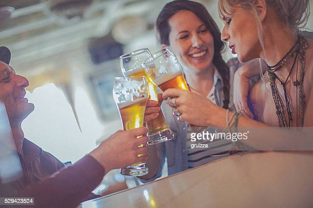 Cheerful friends enjoying time drinking beer together in bar