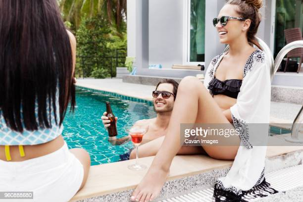 Cheerful friends enjoying vacation at poolside