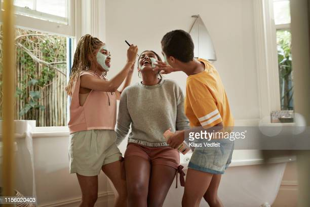 cheerful friends enjoying while applying cream - vanity stock pictures, royalty-free photos & images
