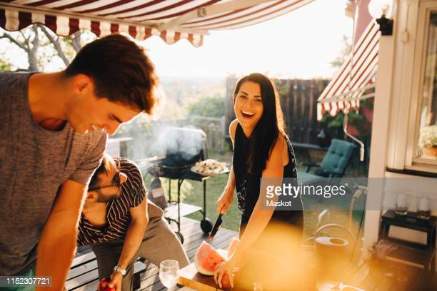 cheerful friends enjoying with fruits while preparing for dinner party - summer party stock pictures, royalty-free photos & images