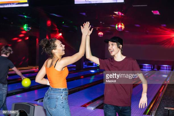 cheerful friends giving high-five on parquet floor at bowling alley - ボーリング場 ストックフォトと画像