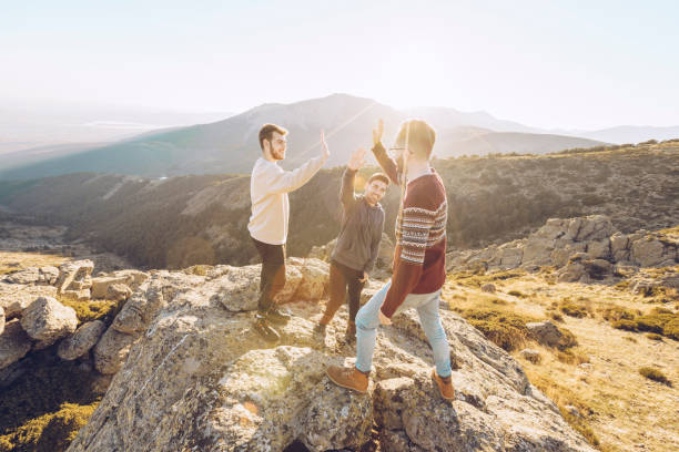 Cheerful friends giving high-five to each other while standing on mountain during sunny day