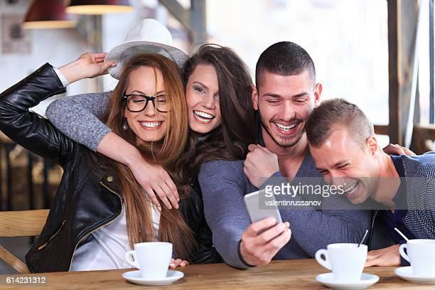 Cheerful friends having fun and taking selfie