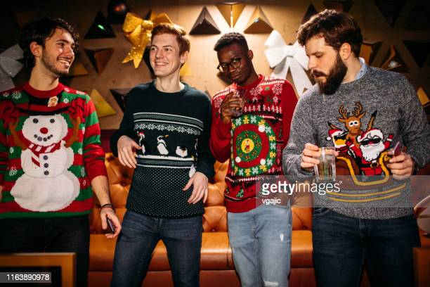 cheerful friends having fun in nightclub. they are wearing christmas sweaters. - christmas sweater stock pictures, royalty-free photos & images