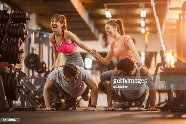 Cheerful friends having fun on a sports training at gym.