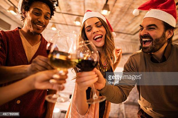 Cheerful friends having fun while toasting with wine at Christmas.