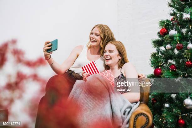 バック グラウンドでクリスマスの装飾と selfie を持つ陽気な友人。