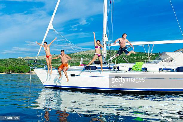 cheerful friends jumping off a yacht
