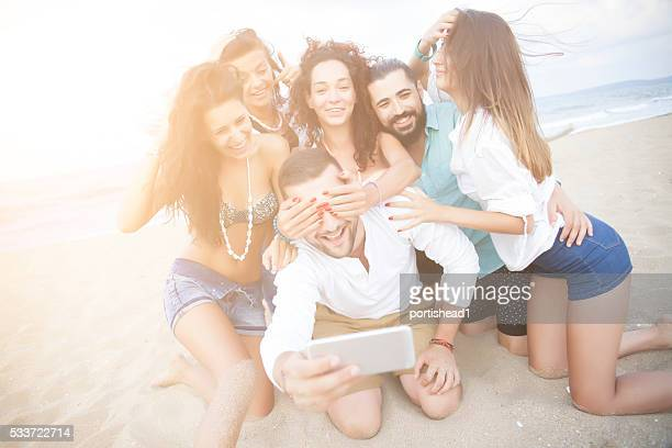 Cheerful friends making selfe on sand