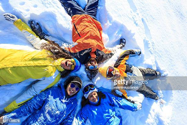cheerful friends making snow angels - snow angel stock photos and pictures