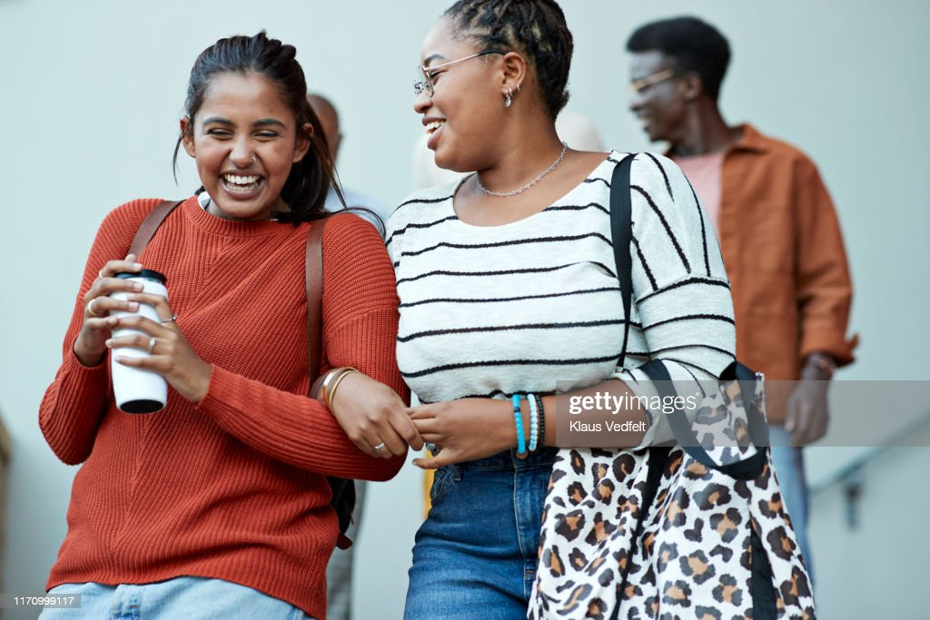 cheerful friends moving down arm in arm at campus : Stock Photo