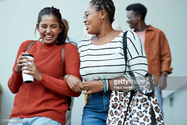 cheerful friends moving down arm in arm at campus - community_college stock pictures, royalty-free photos & images