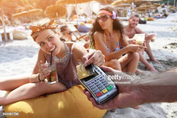 cheerful friends on beach - credit card purchase stock pictures, royalty-free photos & images