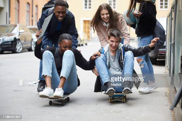 cheerful friends pushing teenagers sitting on skateboard - teenagers only stock pictures, royalty-free photos & images