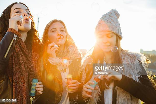 cheerful friends relax together with blowing soap bubbles