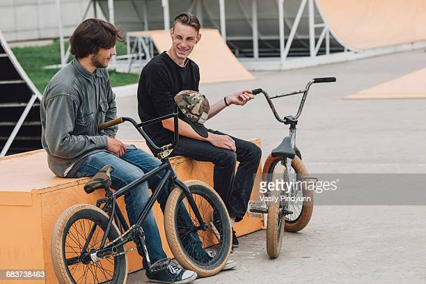 Cheerful friends resting on seat with bicycles at skateboard park