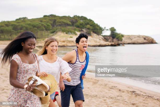 Cheerful friends running on beach during vacation