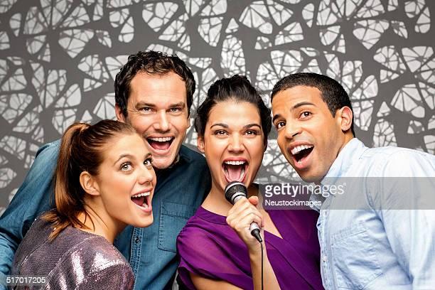 Fröhlich Freunde mit Mikrofon singen Karaoke im Nightclub