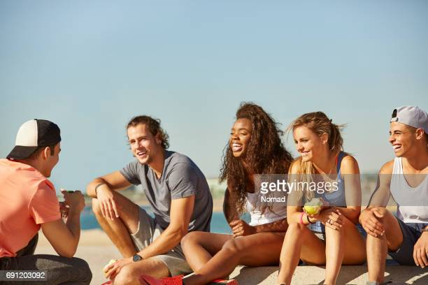 Cheerful friends sitting at beach against sky