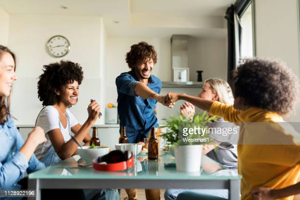 cheerful friends sitting at dining table - five people stock pictures, royalty-free photos & images